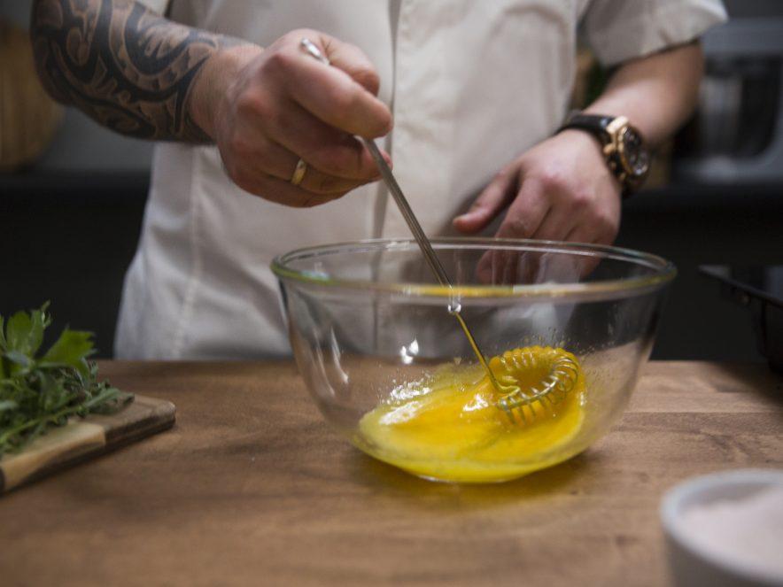 Visper egg og sitronjuice i en glassbolle